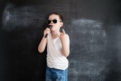 Young boy`s standing near blackboard singing in microphone. Rockstar. Creative design concept for 2019 calendar. Young boy`s standing near blackboard singing in royalty free stock photo