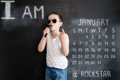 Young boy`s standing near blackboard singing in microphone. Rockstar. Creative design concept for 2019 calendar. January.  stock image