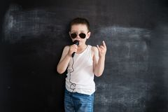 Young boy`s standing near blackboard singing in microphone. Rockstar. Creative design concept for 2019 calendar.  stock photo