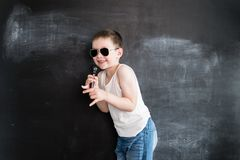 Young boy`s standing near blackboard singing in microphone. Rockstar. Creative design concept for 2019 calendar. Young boy`s standing near blackboard singing in royalty free stock image