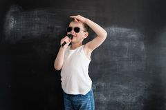 Young boy`s standing near blackboard singing in microphone. Rockstar. Creative design concept for 2019 calendar. Young boy`s standing near blackboard singing in stock image