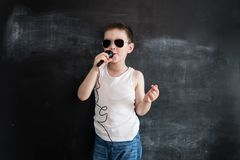 Young boy`s standing near blackboard singing in microphone. Rockstar. Creative design concept of future profession. royalty free stock photos