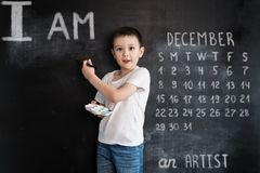 Young boy`s standing with palette and brush in his hands near blackboard. Young artist. Creative design concept for 2019. Calendar. December royalty free stock photos