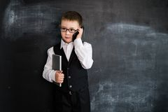 Young boy`s standing with phone and notebook in his hands near blackboard. Young businessman. Creative design concept for 2019 ca. Lendar stock photography