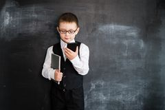 Young boy`s standing with phone and notebook in his hands near blackboard. Young businessman. Creative design concept for 2019 ca. Lendar royalty free stock image