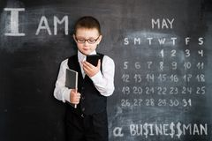 Young boy`s standing with phone and notebook in his hands near blackboard. Young businessman. Creative design concept royalty free stock image