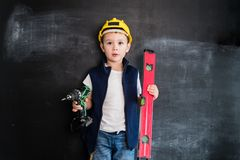 Young boy`s standing with screwdriver near blackboard. Young builder. Creative design concept for 2019 calendar. Young boy`s standing with screwdriver near royalty free stock photography