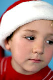 Young boy in a santa hat. On blue background Stock Photos