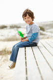 Young boy sat on beach with windmill Stock Images