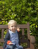 Young boy sat on bench Stock Image