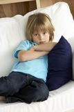 Young Boy Sat on Sofa at Home Royalty Free Stock Photo