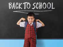 Young boy in school uniform infornt of black board with `back to school` written in white chalk. He has arms raised up doing muscle man pose royalty free stock photos