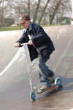 Young Boy on Scooter. Boy rolling down skate ramp on two wheeled scooter. Boy has jacket and baseball style cap royalty free stock photos