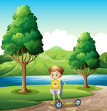 A young boy with a scooter standing near the river Stock Image