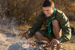 Young Boy Scout Cooking for Food on the Ground. Happy Young Boy Scout Grilling Sausages For Food to Eat on the Ground at the Camp Area Royalty Free Stock Photos