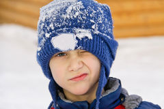 Young boy screw up ones eyes. In blue cap with snow Stock Photo