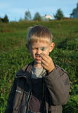 Young boy screw up ones eyes. Looking on the dandelion Royalty Free Stock Photography