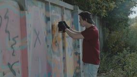 Young boy secretly drawing colorful graffiti on street wall. 4K stock footage