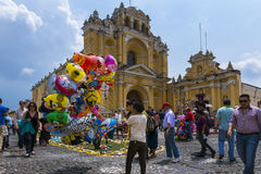 Young boy selling baloons in a street of the old city of Antigua with the San Pedro Hospital on the background, in Guatemala Royalty Free Stock Image