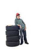 Young boy with a set of car tires. Ready to change them - isolated on white royalty free stock photography