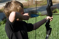 Young Boy Shooting Arrow. Young boy with the arrow ready to shoot the target stock photography