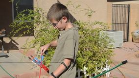 Young boy shooting a bow and arrow stock footage