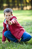 Young boy shooting with pointing finger at camera Stock Images