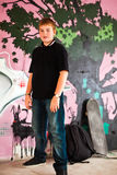 Young boy with shoulder bag. And skateboard and graffiti wall in background Royalty Free Stock Photos