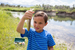 Young boy showing the fish he caught. Royalty Free Stock Photos