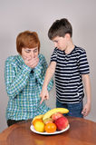 Young boy showing fruit to a woman Royalty Free Stock Image