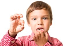 Young boy showing his first lost milk-tooth. In his hand, isolated on white background royalty free stock photo