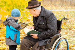 Young boy showing his grandfather his tablet. Young boy showing his grandfather something on his tablet computer as the old men sits in a wheelchair in his Stock Photos