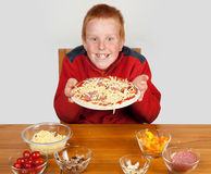 Young boy showing off made pizza Royalty Free Stock Photo