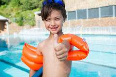 Young boy showing thumbs up at poolside Stock Image