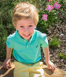 A young boy shows happiness as he explores the sights at a public garden Stock Photos