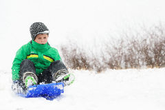 A young boy shows his excitement sledding down a hill Royalty Free Stock Images