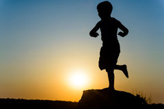 Young boy silhouetted by the sunset Stock Photography