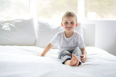 Young Boy sit on bed at home stock photo