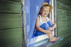 Young boy sit on the window sill. Outdoor portrait: Young boy sit on the window sill Stock Image