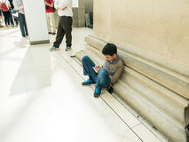 Young boy sits against Great Court wall playing with smart phone Royalty Free Stock Image