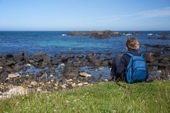 Little boy with blue backpack, sits on ground at irish coast rock, next to the sea royalty free stock image