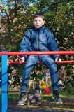 Young boy sits on the monkey bar Royalty Free Stock Images