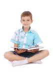 The young boy sits near the open book Stock Image