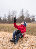 A young boy sits on the sawdust with his hand raised up Stock Images