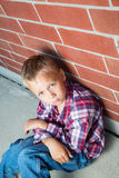 Young Boy Sitting Against a Wall Royalty Free Stock Photos
