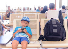 Young boy sitting in an airport terminal Royalty Free Stock Photos