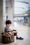 Young boy sitting alone in a hallway Stock Image