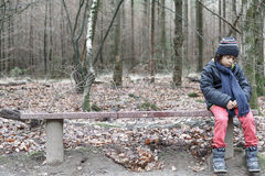 Young boy sitting alone on a rustic bench. Young boy sitting alone on a rustic wooden bench looking down at the ground with a sad wistful expression through stock image