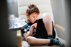 Young boy sitting in armchair and holding a tablet. Spying throu. Gh the door opening. Daily technology for playing and learning. Consept of children using Royalty Free Stock Photo