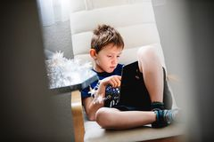 Young boy sitting in armchair and holding a tablet. Spying throu. Gh the door opening. Daily technology for playing and learning. Consept of children using Stock Photo